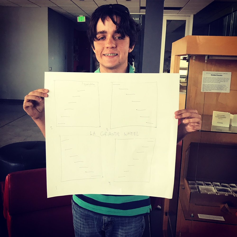 Weekend Workshop Student-Writer Christian holds up a plan for his poem based on the La Grande Ferris Wheel.