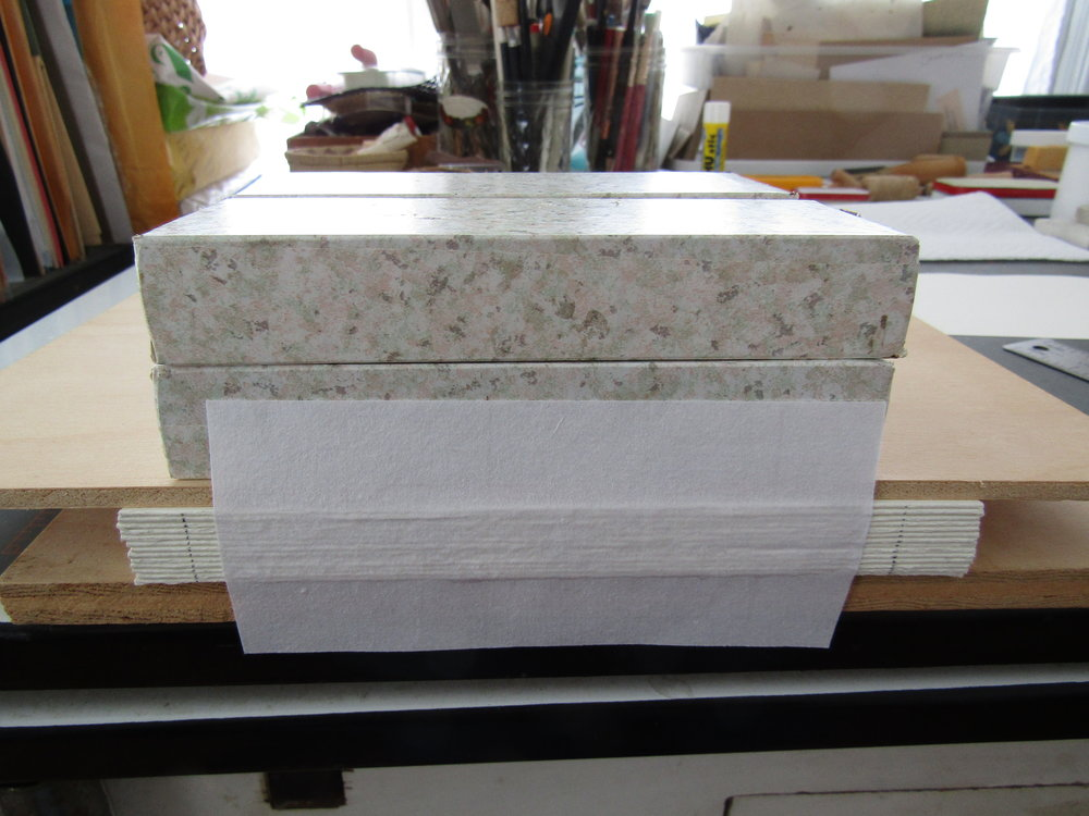 The pages are folded and weighted. A piece of Japanese paper is adhered to the spine. This will be hidden when the cover boards and outer spine are added.