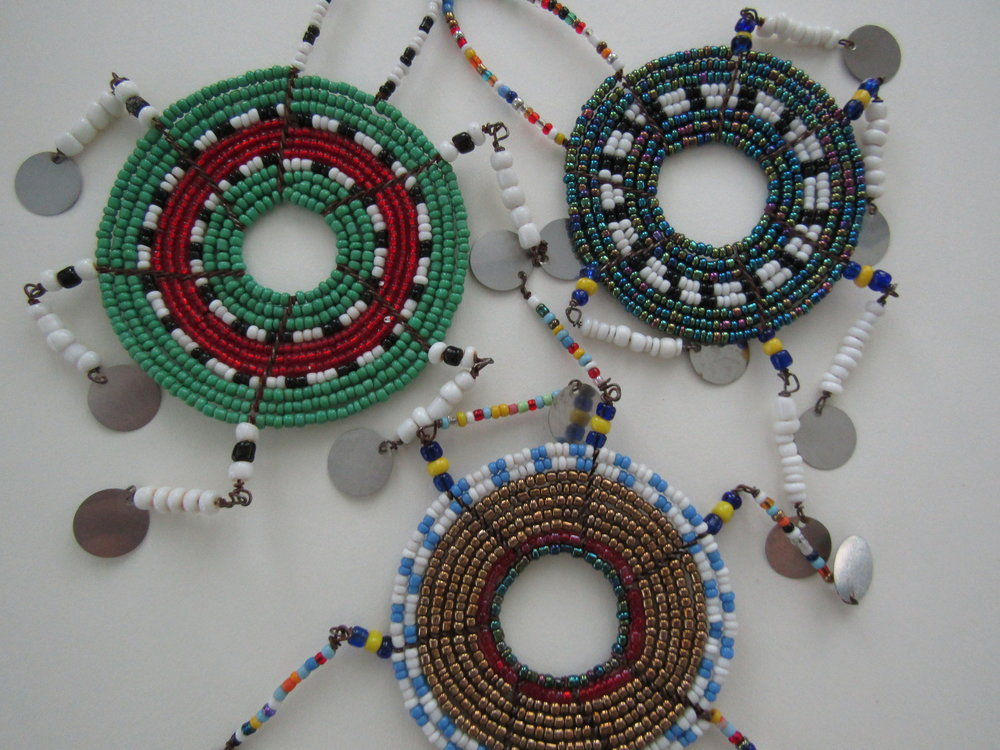 The Maasi women make these ornaments using delicate wire combined with various seed beads and metal disks.