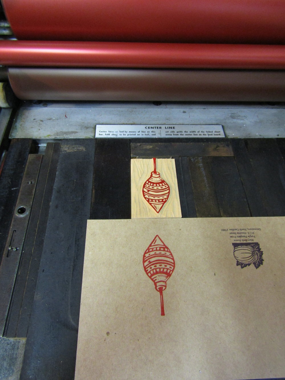 I printed the ornament in red on chipboard. Here the block is set in place on my Vandercook.