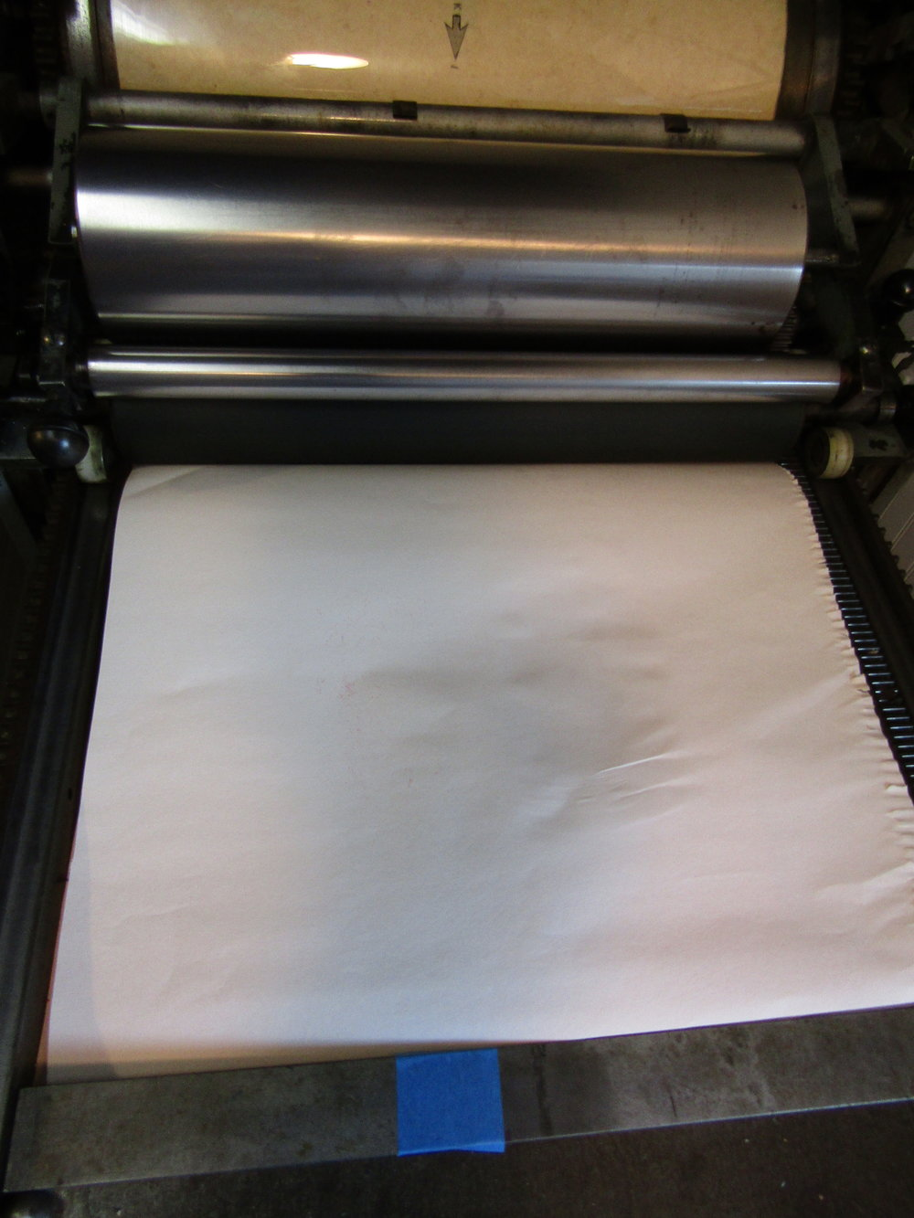 I cover the towel arrangement with newsprint as a way of keeping it clean. I then roll the cylinder and rollers over this set-up and print.