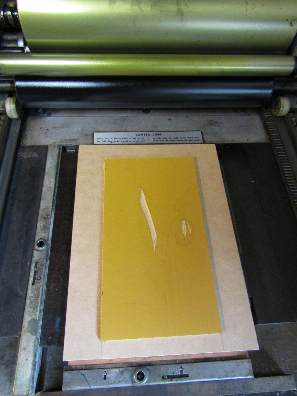 "The press and linoleum are inked and ready for the first run, a pale yellow color. I am printing on Rives BFK paper. I place the unmounted linoleum on a wooden base using permament double sided tape. Shims of chipboard are under the wood to get the linolem type high which is .918 "".  Each time I print a new color, more of the block is carved away and more details are added to the image. This is the reason it is called a Reduction print."