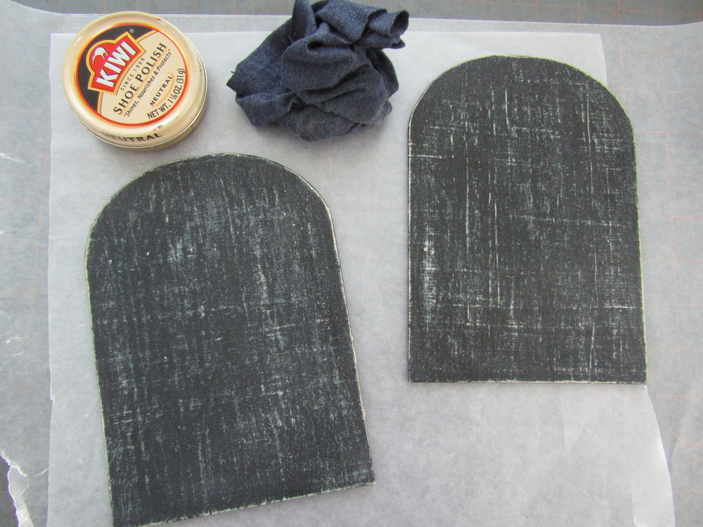 I cut Davey board into the arch shape; then covered it with papyrus. Layers of milk paint in various colors (the final layer of paint was black) were applied to the papyrus. Once the layers of paint were dried and sanded; shoe polish was applied and rubbed with a soft cloth giving the covers and smooth polished surface.