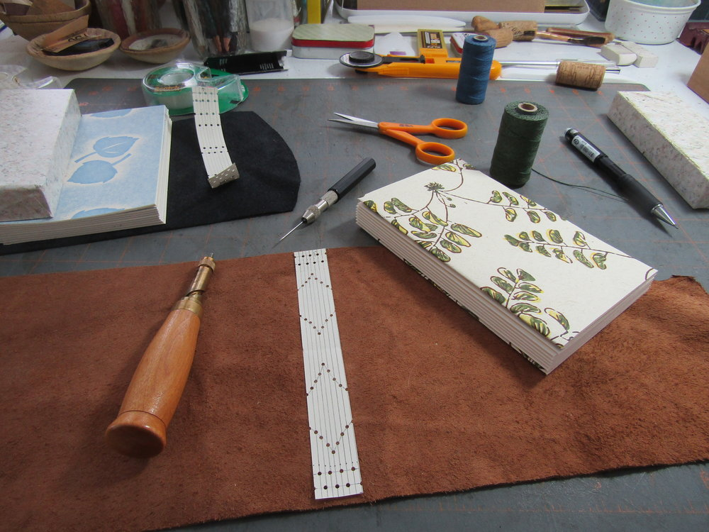 Prepared text blocks with leathers, threads, and spine designs. The designs will be a decorative element on the sewn spines of the books. They are also the sewing pattern for the books. I will use the Japanese Drill Punch for punching holes into the leather and the awl to place holes (sewing stations) in the paper sections.