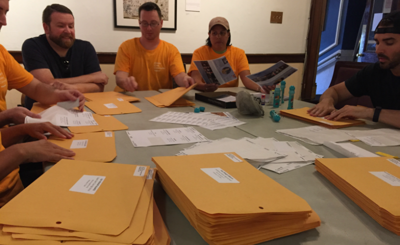 A group from vanguard puts together a mailing for local colleges during a recent day of service.