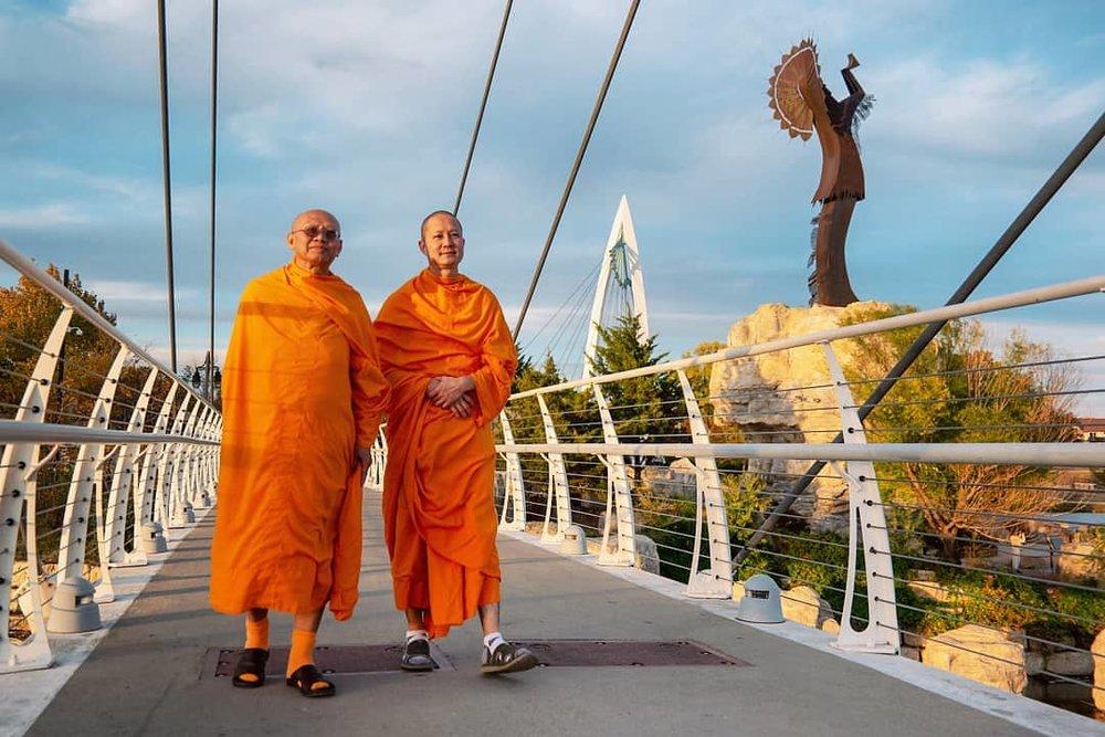 A pair of Buddhist monks cross the bridges at Keeper of the Plains, Wichita, Kansas.