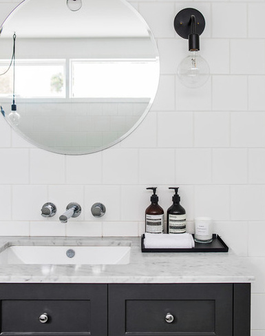 this bathroom embodies monochromatic simplicity with a large round mirror providing a great dynamic to the square tiles