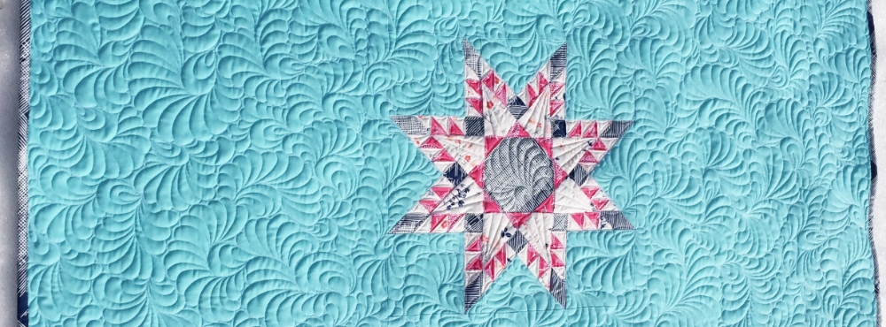 "The feathered star block is shown here at 16"" square, I surrounded it with solid fabric to make a one-block baby quilt. Psst! I made a video showing how I draw/quilt those fancy feathers in the background  here ."