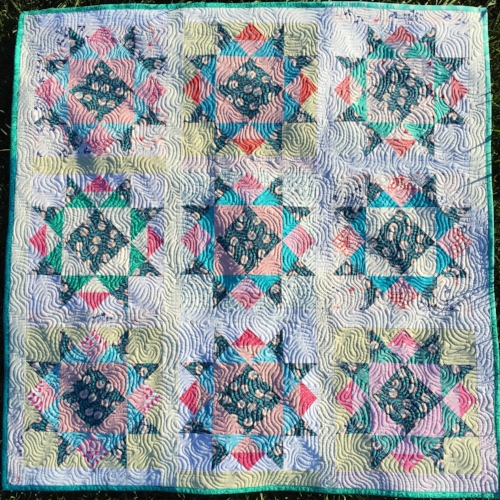 In this version, I used the blocks set together with a narrower sashing and borders to make a baby quilt. I also loved how the scrappy look worked so well with this pattern! :) See my video tutorial for the quilting design shown here, called Ripples.