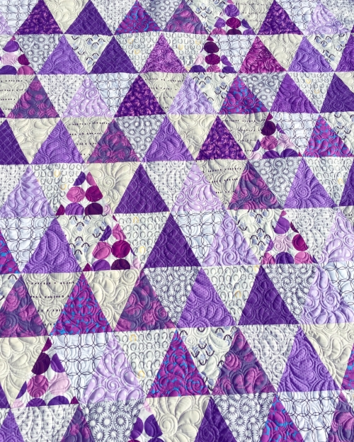 Purple triangle quilt made with  Tri-Recs  rulers, free-motion quilting tutorial here:  feathered spirals