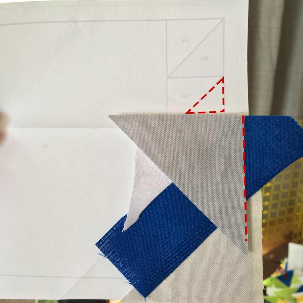 "When I'm piecing spines, I think in terms of covering the ""upright"" triangle (outlined in red dashed lines). I make sure the new triangle is ""leg-down"". Also, it's important to note that I'm making sure I cover the 1/4"" seam allowance on both the right (unmarked) and left side of this spine."