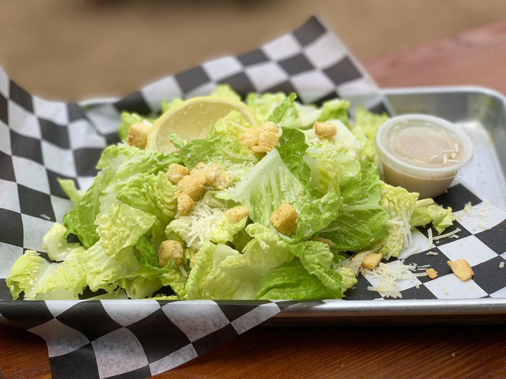 Caesar Salad - parmesan cheese, croutons and a lemon on a bed of romaine lettuce with caesar dressing