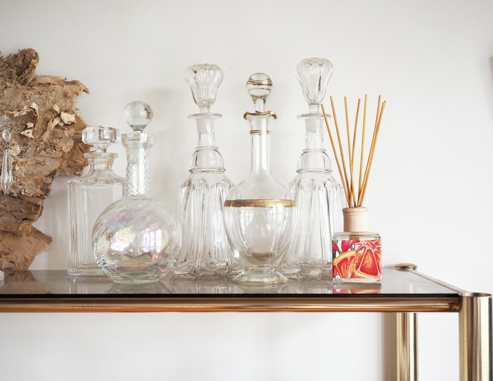 In our house, a collection of vintage lead crystal decanters are set near a window, and catch the morning light in a sparkly display.