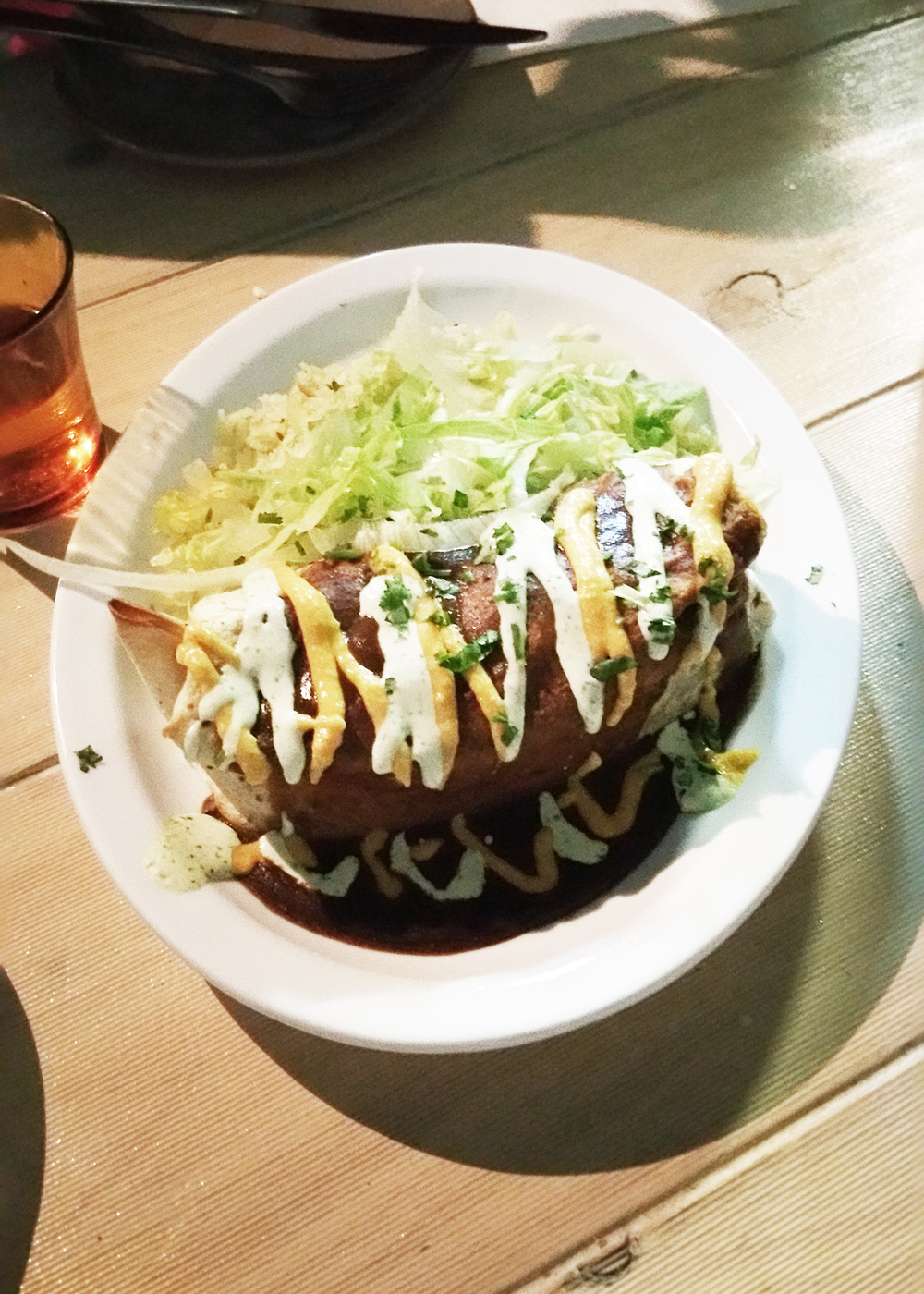 Carnitas Burrito: filled with 'pulled pork' carnitas and spiced black beans, served wet-style with red enchilada sauce, coriander cream and melty cheese on top. Served with coriander & lime rice on the side.