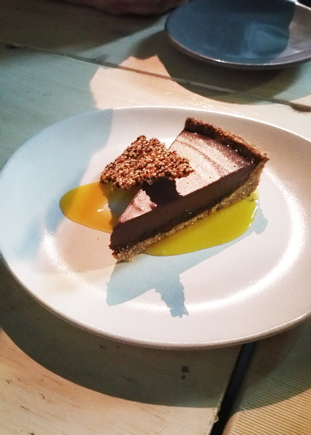 Tarta de Chocolate : rich dark chocolate tart with a layer of chipotle & ancho chilli caramel & a hazelnut crust. Served with passionfruit gel & crunchy quinoa brittle.