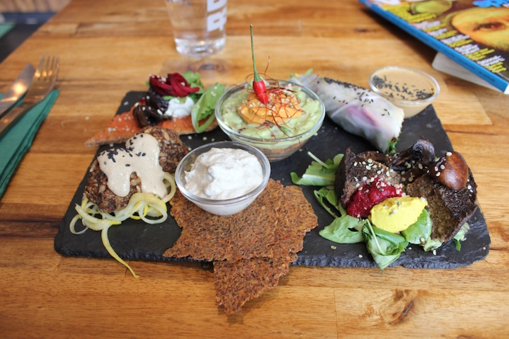 Raw Tasting Plate at Rawtastic featuring raw pizza, tex mex bowl, rainbow rolls, mushroom burger, falafel, flax crackers & cashew cheese.