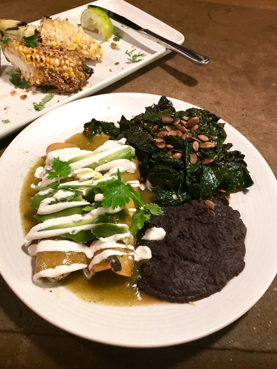 Enchiladas Verdes at Gracias Madre vegan restaurant in the San Francisco Mission District.  Tortillas filled with potato, zucchini and peas topped with tomatillo salsa, nut-based crema and avocado. Served with sautéed greens and beans.