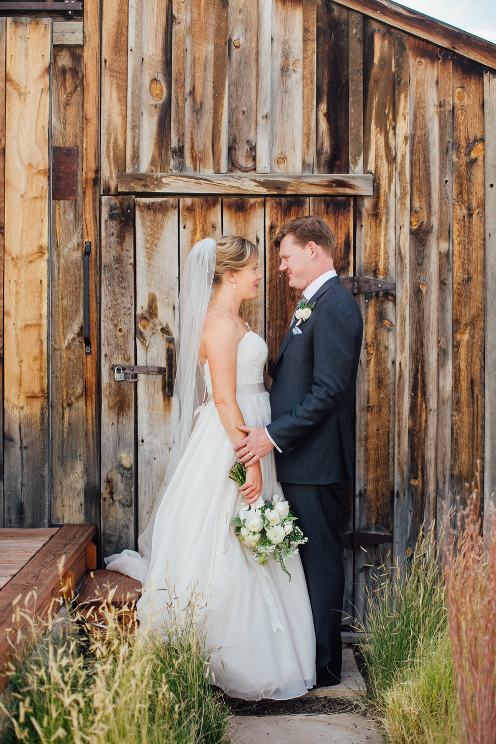 Bride and Groom Couple with White Wedding Bouquet, Wooden Barn  Little Thompson Valley Pioneer Museum Berthoud Colorado Wedding
