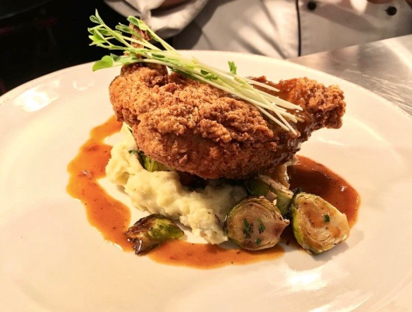 farmhouse fried chicken with yukon gold mashers, bacon braised brussels, and shiner bock demi.  PHOTO COURTESY OF KIRAN BALAN.