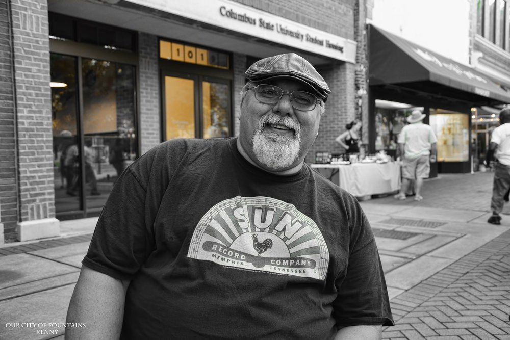 """There are hidden gems in every city. People who have contributed their passion and soul into the city they live in for years. Kenny, is surely one of our gems. I've known this man for years, and every time I see him…I just can't help but to smile. A talent filled giant with a heart of gold; it's people like him that put faith back into humanity for me. This, is his story.  """"Hey guys, my name is Kenny Miller. People around Columbus, Georgia know me as a musician. I play lead vocals, percussion and harmonica in my band Haywire. I'm also the percussionist, harmonica player in another local band The Breakdowns, the Tom Petty Tribute Band.""""  """"You had a big show lately here in town.""""  """"We had a blast! We played out in the Civic Center two weekends ago. We opened up for the band Big & Rich. Got a chance to meet the guys and hang out. We got a chance to sound really, really good. The sound guys we had working for us were meticulous in getting our sound quality right. They took the time to get all the levels right and all the monitors right. We weren't just some opening band…it wasn't your wham-bam, you've got your five minutes now get out of here. We got a good sound check so we tore the roof out that sucker. Terri Young…his voice was strong and all the guys in the band…Willie, Kurt, Mike, Emily and Rick…all of these guys were on top of their game that night. We played great songs. We got a great response and we got great reviews, especially from  gigsalad.com.   We've been doing Haywire since '92. We've been around for a long time. We had some personal changes over the years ya' know? But we haven't had a lull in our plans since '92. No more than a couple of months. We are still out there doing our thing and people still seem to show up. """"  - You guys have very faithful followers.  """"Oh we have some of the best fans in Columbus! They're going to come out to the show. They're going to hoop and holler. They're going to make the show great. """""""