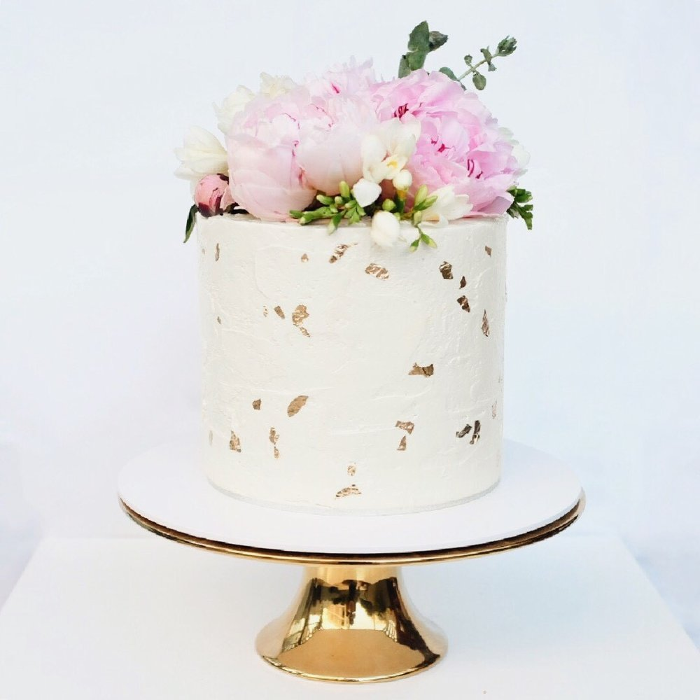 Spring  cake with peonies, eucalyptus and gold leaf