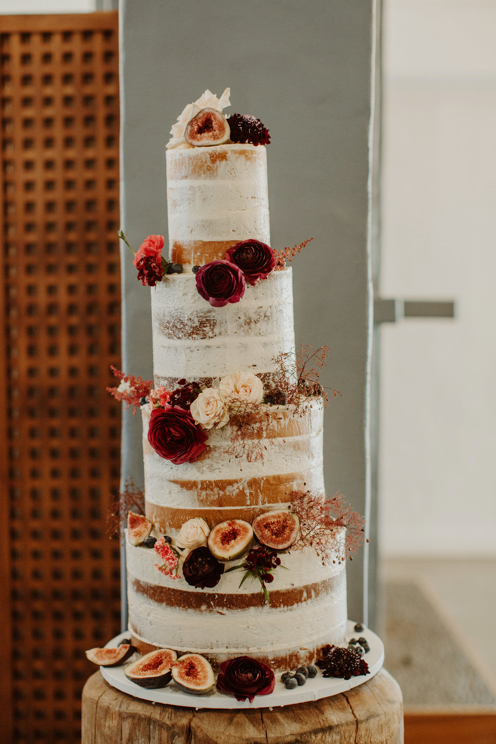Tall naked wedding cake with figs and fresh flowers