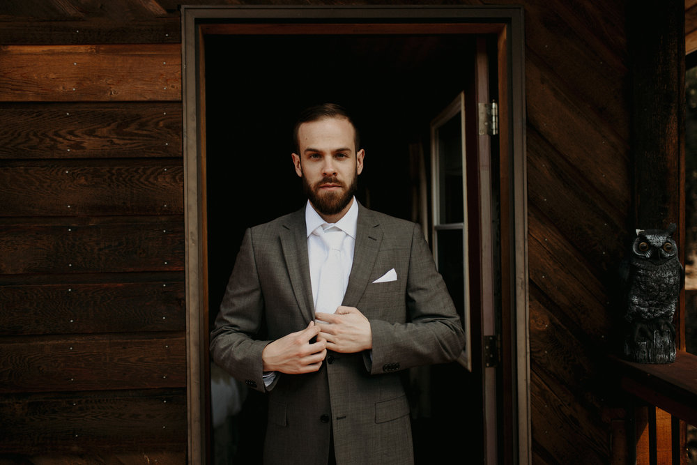 Moody getting ready images of groom in a cabin in the forest | Banff Elopement Photographer Kandice Breinholt