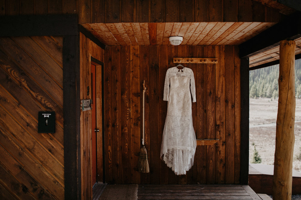 Moody getting ready images of Vera Wang wedding dress in a cabin in the forest | Banff Elopement Photographer Kandice Breinholt