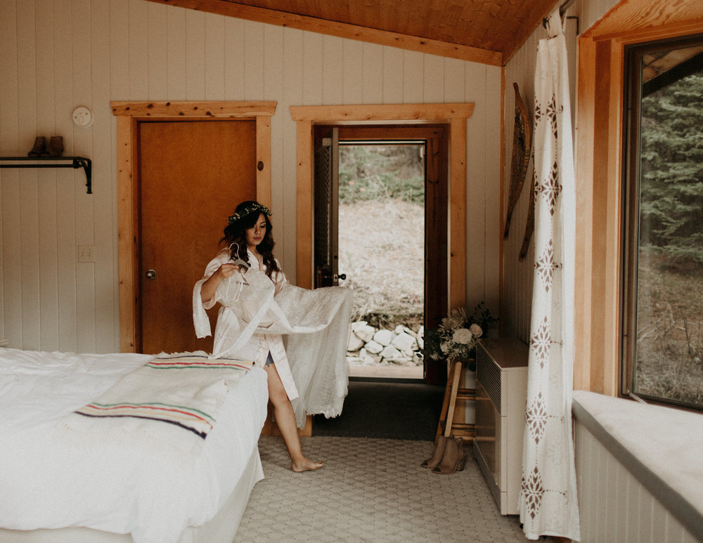 Moody getting ready images of bride in a cabin in the forest | Banff Elopement Photographer Kandice Breinholt