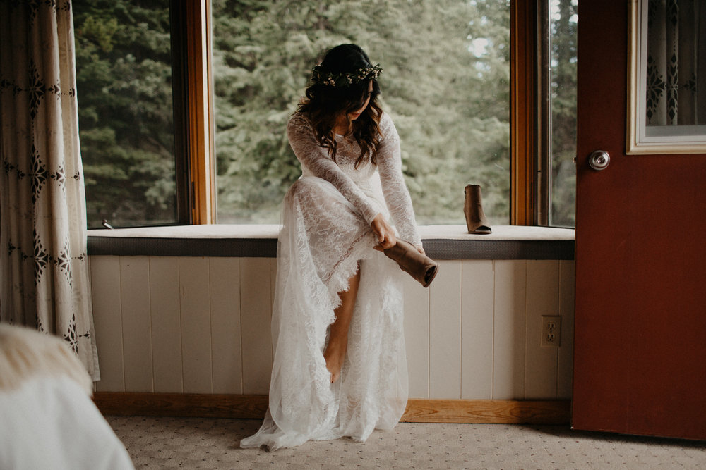 Moody getting ready images of bride in Vera Wang lace dress and Willow Flower Co flower crown in a cabin in the forest | Banff Elopement Photographer Kandice Breinholt