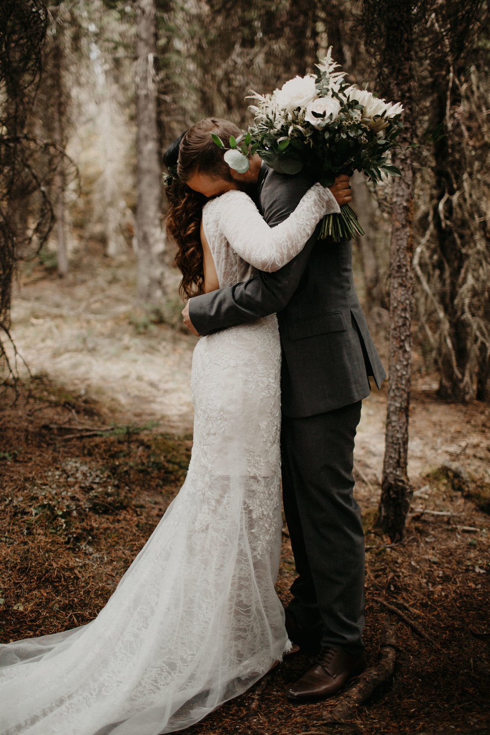 Moody, emotional first look in the forest | Banff Elopement Photographer Kandice Breinholt | Vera Wang lace wedding dress and Willow Flower Co neutral green and white bouquet and flower crown