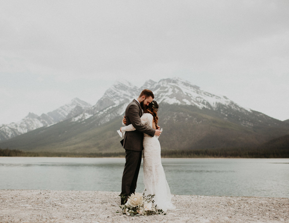 Sharing emotional vows next to a lake | Elope in Banff | Banff Elopement Photographer Kandice Breinholt | Willow Flower Co Bouquet and Flower Crown