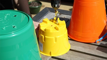 1. Ask an adult to help you drill holes in the bottom of your buckets for drainage.
