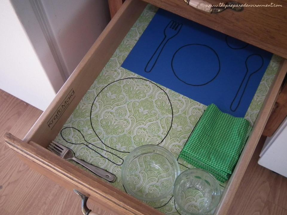 "This drawer has a very clear place for all items needed to set a place at the table.  To make this yourself, gather all the materials to be arranged, and lay them out in a drawer, cabinet, or bin.  When you are happy with the arrangement, create a ""map"" or control of error for where everything goes.  In this case, the drawer was lined with shelf paper, and then all items were outlined in black marker."