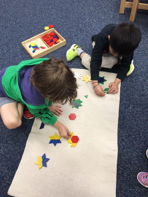 During this last week of school the students enjoyed some free choice activities in Primary 1 classroom.  Two Kindergarteners decided to work on pattern tiles and made stars on the rug to create their own galaxy.