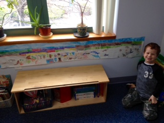 A Lower Elementary West student proudly posed next to his completed and handmade Timeline of Life.  The Timeline of Life is an entire representation of the life on Earth beginning with the Paleozoic Era all the way through to the Cenozoic Era.