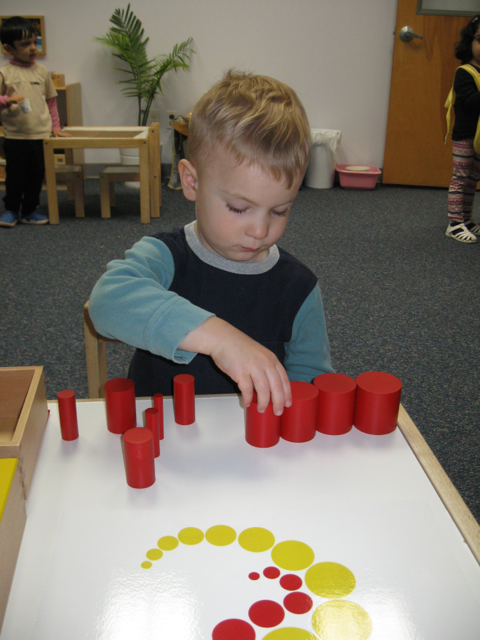 Montessori Sensorial materials often invite the child to focus on a single concept or skill, such as grading objects by size.  Once the child masters the basic idea, he or she can begin to explore extension activities that expand and reinforce existing knowledge.  Using familiar materials like the colored Cylinders, the Toddler 2 students are enjoying the challenge of extension activities like these pattern cards.  This activity requires a long sequence of steps: first, grading the Red Cylinders by width; then, grading the Yellow Cylinders by size; and finally matching the Cylinders to the intricate patterns on the cards.