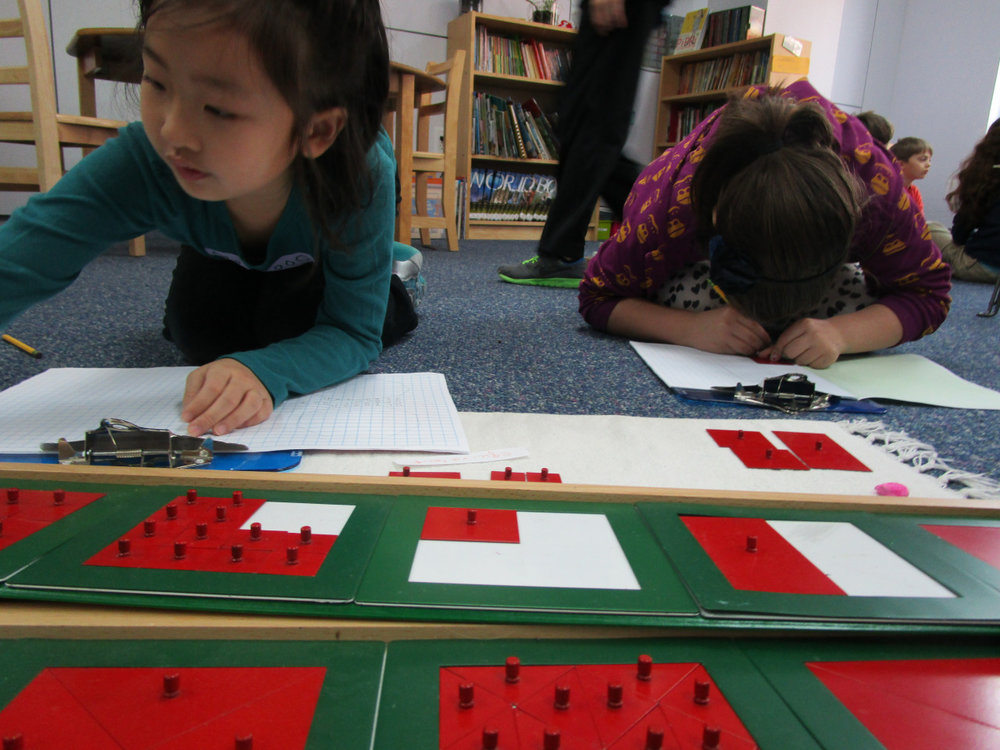 Two Lower Elementary North students worked with various fraction insets to create designs and label their values.