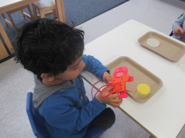 Enjoying one of this week's popular Practical Life activities, a Primary 1 student wove his way through the wooden bear, which required fine motor skills and concentration.
