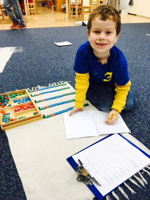 A second grade Lower Elementary West student worked on division using the Stamp Game, a material that offers the student a concrete understanding of Math operations.
