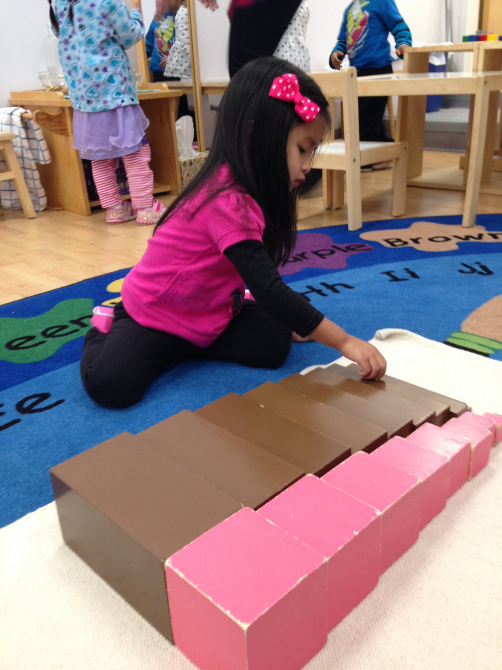 This Toddler 1 student practiced an extension of the classic Montessori materials, the Brown Stair and Pink Tower.  This exercise requires twenty careful trips back and forth to bring the blocks one by one to a work mat.  This part of the process alone is a wonderful opportunity for working the body as well as the mind!  Then, the materials are placed in order from thickest/largest to thinnest/smallest. This helps to develop awareness of patterns and discrimination by size using both the visual and tactile senses.
