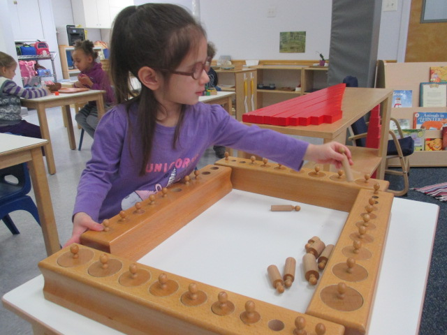 What does a Primary 1 student do when she has mastered the Knobbed Cylinders?  She brings all the four blocks of Knobbed Cylinders out, empties them and tries to fit them all together at once.  This is her own interesting extension of the Knobbed Cylinders material.