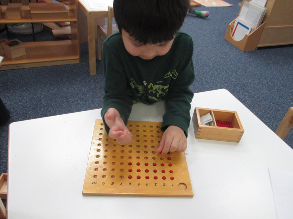 The Kindergarteners challenge themselves everyday with lessons that help them think more and do more.  A Primary 1 Kindergartener worked on the Multiplication Bead Board, which requires tremendous concentration and accuracy.