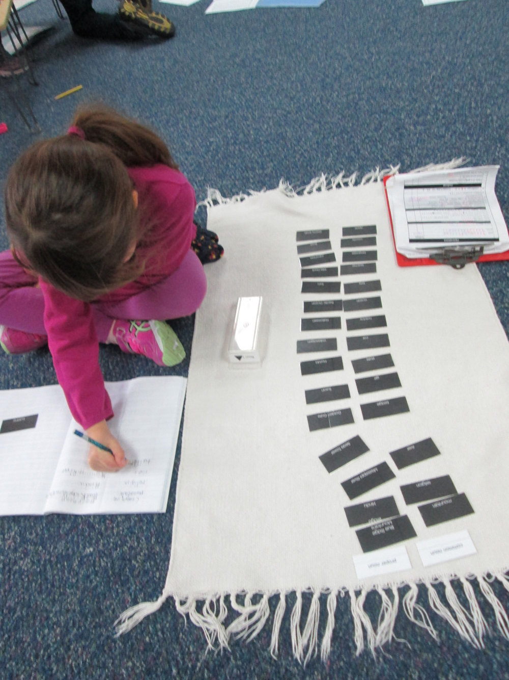 A first grade Lower Elementary East student diligently worked on a follow-up focused on common vs. proper nouns.  This work required the student to sort the cards into their correct categories, write them in the Language notebook and symbolize them.  While this would seem to be a fairly quick and easy task for an adult, it requires each student to maintain focus, dedication and determination.