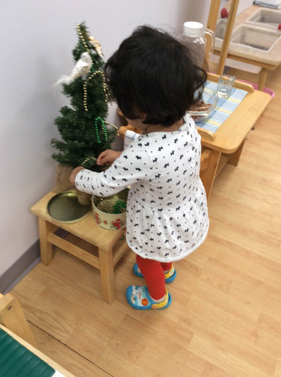 A Toddler 1 student decorated the little classroom Christmas tree, exercising her pincer grip.