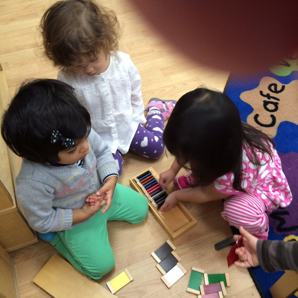 As the Toddler 1 students work on fine motor coordination sometimes color matching turns into a peer lesson about how to fit a lot of tablets back into the box.