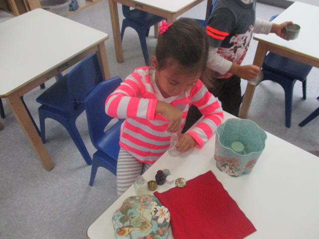 As part of Practical Life work, a Primary 1 student opened and closed bottles to refine fine motor skills.