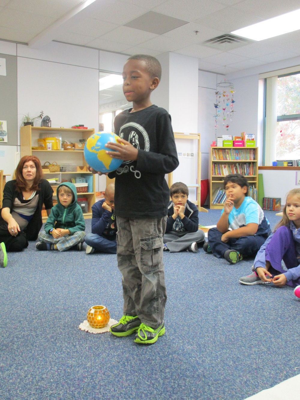 A first grade Lower Elementary North student celebrated his seventh birthday. His mom came to join in the celebration.  They shared about each year of his life as he walked around a representation of the Sun, holding a globe of the Earth.
