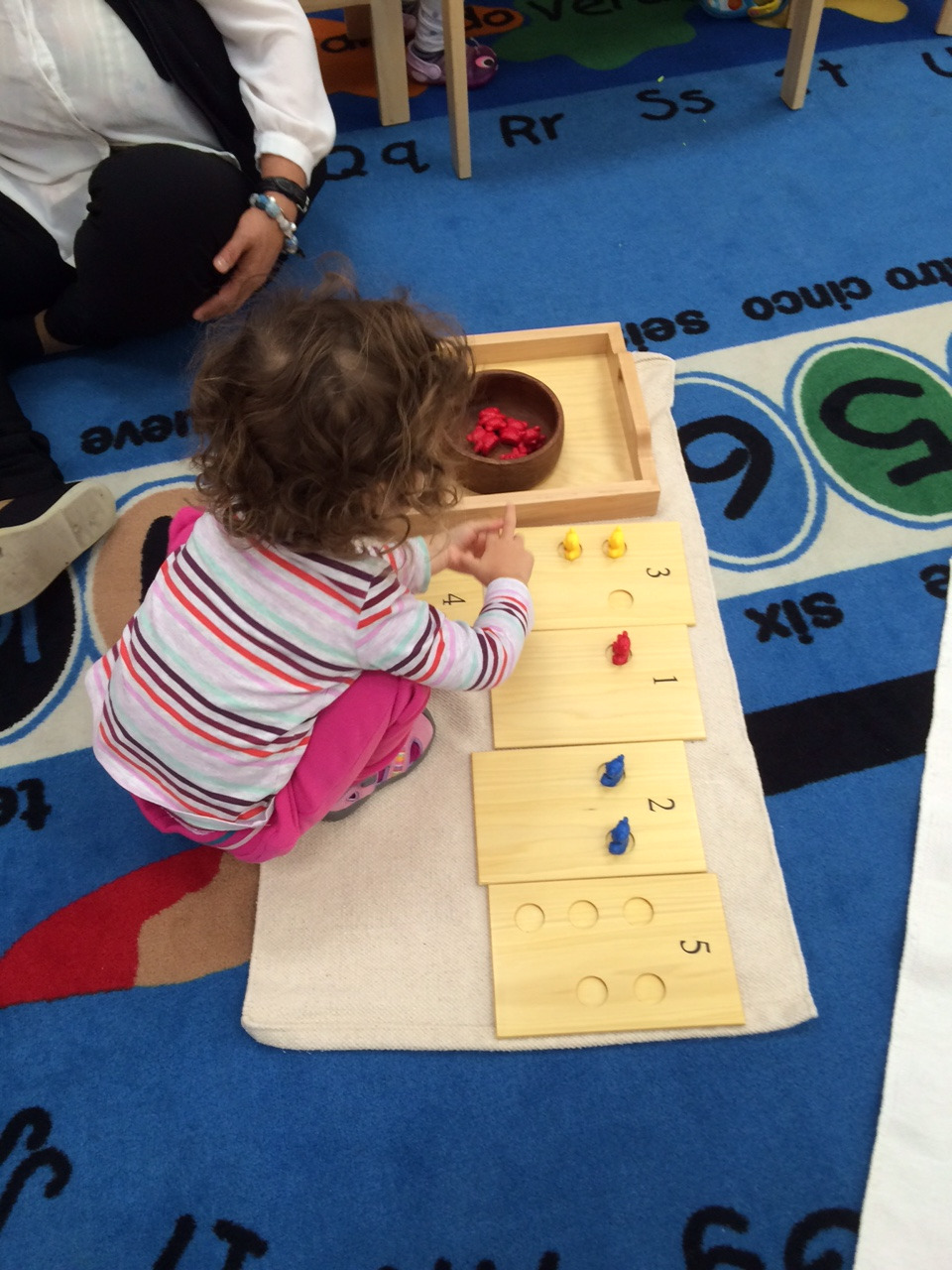 A Toddler 1 student learned about quantities and the numerals that designate quantities.