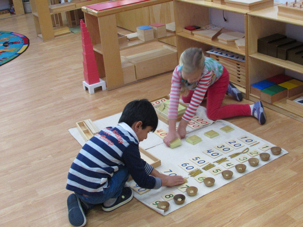 "Two Kindergarteners enjoyed a lesson about the Bird's Eye View.  This work offers the student a ""bird's eye view"" of the association between quantity and written symbols using the cards and beads.  Students also use this material to practice arranging the quantities and numerals."